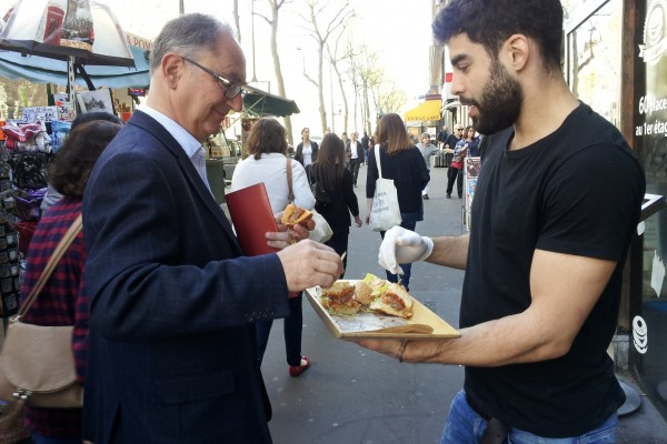 burger bagel. Un homme goûte.