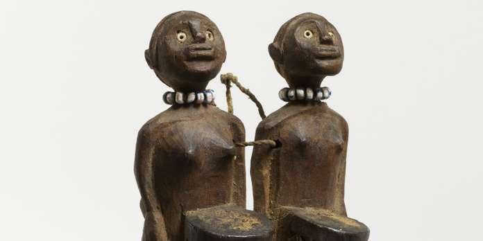 """Sorte de figuration de 2 cornes muhara surmontées de deux personnages (un masculin, un féminin) chacun ayant devant lui un récipient tronçonique rempli de ce qui rend efficace le """"protecteur"""". Colliers de perles de verre. Des perforations sur les côtés servent à faire passer le fil de couture du lien de suspension."""