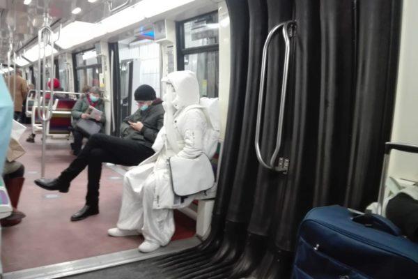Une femme toute en blanc dans le métro parisien.